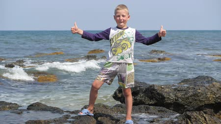 промывали : Boy stands on the rocks washed by the spray of the sea waves. Waves break on the shore. Thumbs up raises the baby.