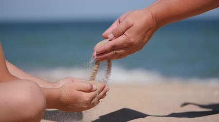 kvarc : Rest on the sea with children. Sand is poured from the palms of the hands into the palms of the child. Stock mozgókép