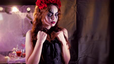 espartilho : Easy Halloween Makeup. The girl with the picture on her face. The devils bride with a wreath of red flowers on her head. The woman is wearing a black corset dress and black stockings. The girl making goo-goo eyes and shows himself.