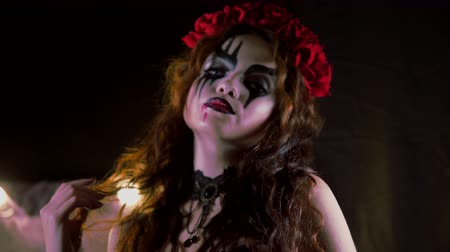 vampiro : Easy Halloween Makeup. The girl with the picture on her face. The devils bride with a wreath of red flowers on her head. The girl making goo-goo eyes and shows himself. Stock Footage
