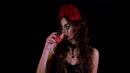 гот : Easy Halloween Makeup. The girl with the picture on her face. The devils bride with a wreath of red flowers on her head. Woman drinks from a glass of red drink offering to drink to the viewer.