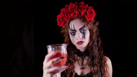 vampiro : Easy Halloween Makeup. The girl with the picture on her face. The devils bride with a wreath of red flowers on her head. Woman drinks from a glass of red drink offering to drink to the viewer.