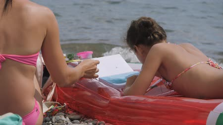 sand paper : Girl draws on the beach. Stock Footage