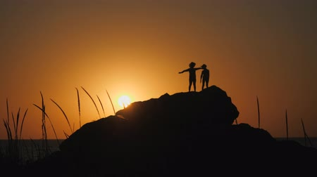 their : Children silhouettes against the sunset. Boys in hats with brims stand on a rock. The stone lies on the shore of the sea. The sun sets behind the horizon. Children waving their hands.