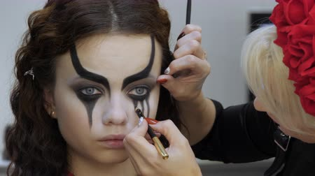 duygusallık : Easy Halloween Makeup. Girl in a beauty salon. Applying a stylistic pattern on the face of the model. The work of a master stylist.