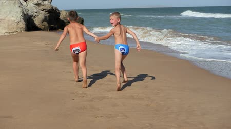 homokóra : Children run along the coastline. Waves wash over the beach. Boys holding hands running along the beach. The kid in the glasses on the rest of the sea. The boy runs and turns back.