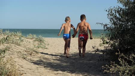 sobre o branco : Children run along the coastline. Waves wash over the beach. Boys holding hands running along the beach. The kid in the glasses on the rest of the sea. The boy runs and turns back.
