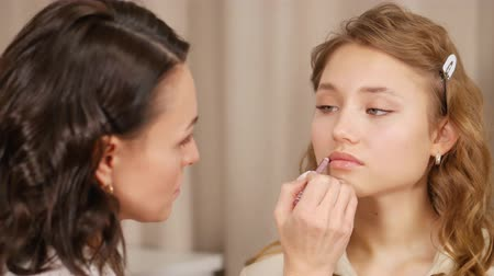 arcszín : Makeup master puts makeup on the face of the client. Applying paint to the lips of the girl.