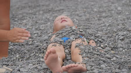 warms : Child lies covered with pebbles. Stock Footage