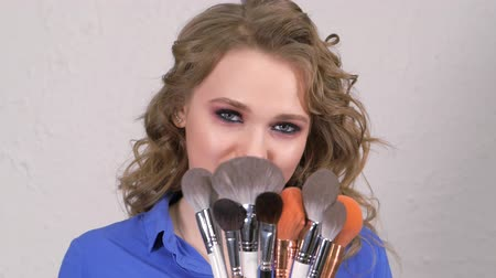 jasně : Young blonde girl hides her lips behind makeup brushes. The face is hidden behind curls of hair. Clearly expressed emotions on the womans face.