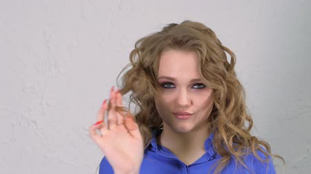 hidden face : Young blonde girl twists a lock of hair around her finger. The face is hidden behind curls of hair.
