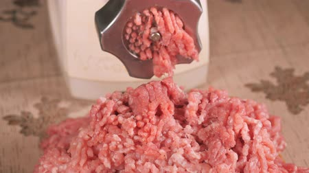 stuffing : Filling comes out through a meat grinder sieve. Meat grinder close up. Pile of chopped meat. Mincer machine with fresh chopped meat. Process of meat grinding in the kitchen with mincing machine. Preparation raw meat for cooking. Force-meat. Cooks hands we