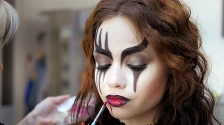 гот : Easy Halloween Makeup. Applying makeup to the face. Drawing red blood on the face of a crying girl. A blood drinker.