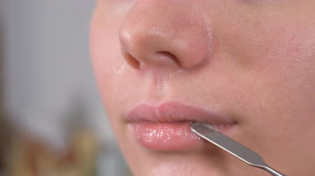 melisa : Preparing the models skin for applying makeup. Lip treatment with a spatula and lip balm. Close up.