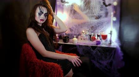 гот : Girl with makeup for Halloween is sitting in front of a mirror. Girl throws her leg over her leg and lifts her skirt with her hand, flirting. Стоковые видеозаписи