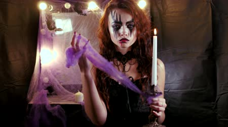 гот : Girl with Halloween makeup approaches the camera holding a burning candle in her hand. Стоковые видеозаписи