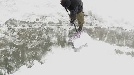overhead view of man shoveling snow on sidewalk Стоковые видеозаписи