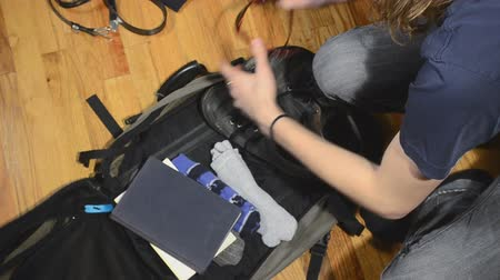 young man packing suitcase quickly
