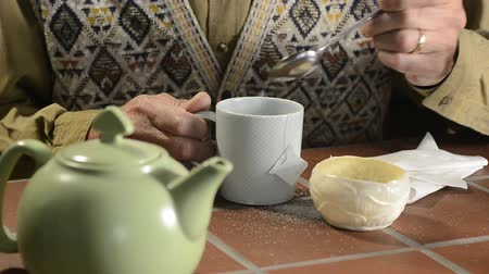 Man with trembling hands preparing a cup of tea