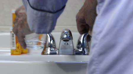man with medication at bathroom sink