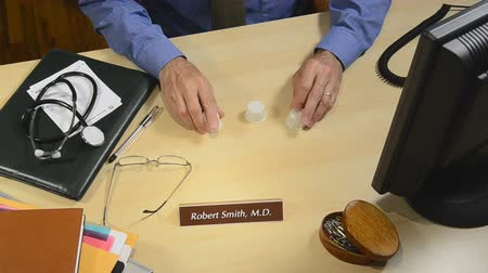 healthy office : physician with pills playing monte game with patient Stock Footage