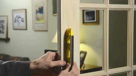 man using carpenter level on installed door Стоковые видеозаписи