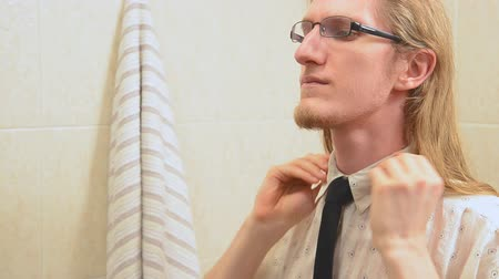 young man looking in mirror adjusting tie   Стоковые видеозаписи