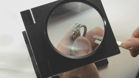 man examining diamond ring under magnifying glass