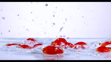 tomates cereja : Falling and splashing cherry tomatoes on water.