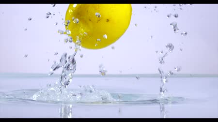 citrón : Lemon slices falling into water, slow motion.