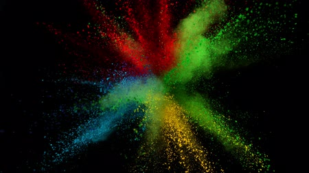 на камеру : Colorful powder exploding on black background in super slow motion.