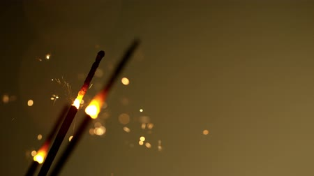 csillagszóró : Burning sparklers on dark golden background. Super Slow Motion. Stock mozgókép