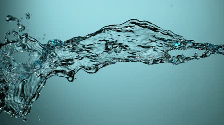 isoleren : Water splashing on blue background, super slow motion. Filmed on high speed cinema camera. Stockvideo