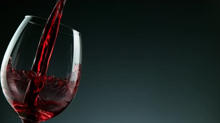 Бордо : Super Slow Motion Detail Shot of Pouring Red Wine from Bottle on dark Background.