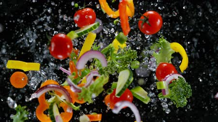 colidir : Fresh vegetables with water droplets exploding on black background.