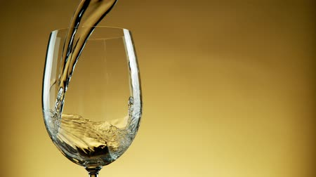 ボルドー : Super Slow Motion Detail Shot of Pouring White Wine from Bottle on golden Background. 動画素材