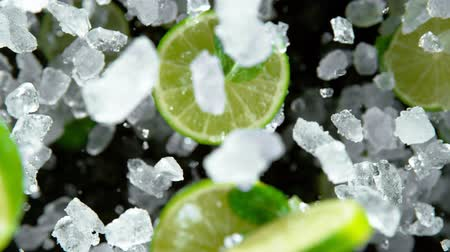 ice crushed : Super Slow Motion of exploding crushed ice with limes towards camera