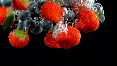 black raspberry : Falling berries into water on a black background.