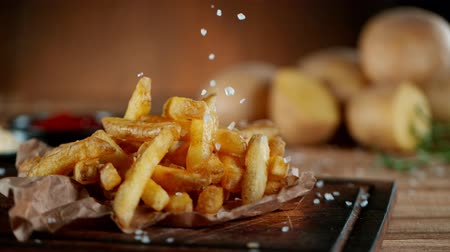 frites : Super Slow Motion Shot of Falling Fresh French Fries on Wooden Table