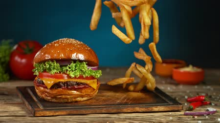 кунжут : French fries fall next to cheeseburger, lying on vintage wooden cutting board. Super Slow motion