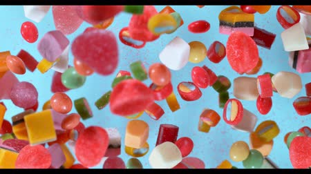 yermantarı : Sweet candies flying in slow motion against pastel background. Filmed on high speed cinema camera