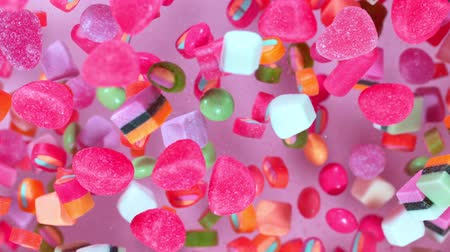 торжества : Sweet candies flying in slow motion against pastel background. Filmed on high speed cinema camera