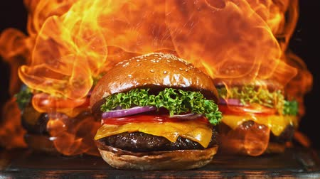сумки : Tasty cheeseburger, lying on vintage wooden cutting board with fire flames in background. Super Slow motion Стоковые видеозаписи