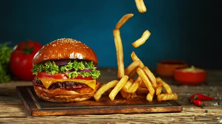 saŁata : French fries fall next to cheeseburger, lying on vintage wooden cutting board. Super Slow motion