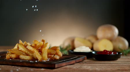 Super Slow Motion Shot of Falling Fresh French Fries on Wooden Table