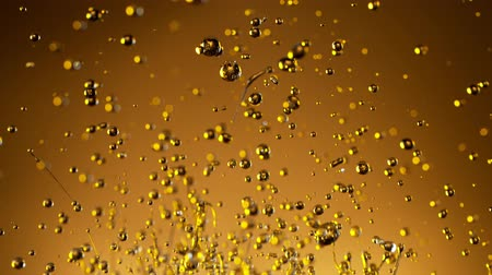 Super Slow Motion Shot of Splashing Oil on Golden Background Vídeos