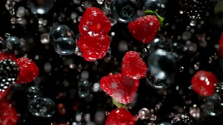 Falling berries into water on a black background.