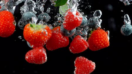 vibráló : Falling berries into water on a black background.