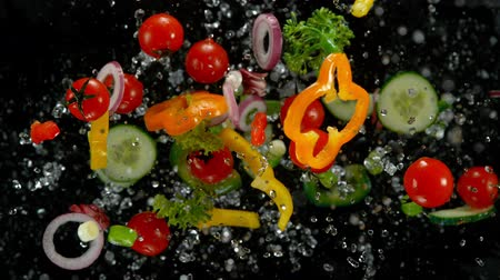 Fresh vegetables with water droplets exploding on black background.