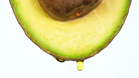 Fresh cut avocado with oil stream. Concept of healthy fruit also useful in cosmetics. Vídeos